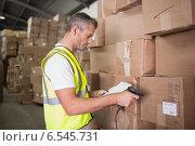 Worker scanning package in warehouse. Стоковое фото, агентство Wavebreak Media / Фотобанк Лори