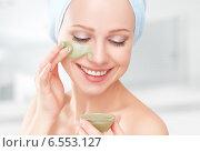 Купить «Красивая девушка наносит косметическую маску на лицо», фото № 6553127, снято 16 октября 2014 г. (c) Евгений Атаманенко / Фотобанк Лори