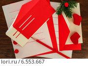 Новогодняя открытка- письма Санте Клаусу с листами бумаги, красными и желтыми конвертами, карандашом, веткой ели, красными бусинами и валенками на деревянном фоне. Стоковое фото, фотограф Marina Kutukova / Фотобанк Лори
