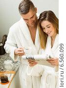 Купить «Cute couple in their bathrobes at breakfast», фото № 6560099, снято 11 июня 2014 г. (c) Wavebreak Media / Фотобанк Лори