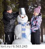 Купить «Счастливая пара делает снеговика», фото № 6563243, снято 16 марта 2014 г. (c) Барковский Семён / Фотобанк Лори