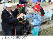 Маленькая девочка дарит ветерану цветы в День Победы (2013 год). Редакционное фото, фотограф Анна Алексеенко / Фотобанк Лори