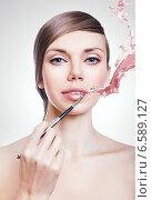 woman with brush on lips and paint splash. Стоковое фото, фотограф Александр Буц / Фотобанк Лори