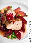 Запеченная свинина с глазированными яблоками, горохом и ягодами красной смородины на тарелке. Стоковое фото, фотограф Анна Курзаева / Фотобанк Лори