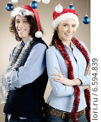Купить «Portrait of a young woman and a man wearing Christmas caps.», фото № 6594839, снято 7 июля 2020 г. (c) BE&W Photo / Фотобанк Лори