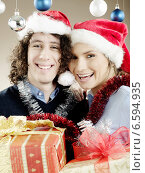 Купить «Portrait of a young woman and a man with presents, wearing Christmas caps.», фото № 6594935, снято 13 июля 2020 г. (c) BE&W Photo / Фотобанк Лори