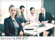 Купить «businesswoman in office with team on the back», фото № 6599811, снято 9 ноября 2013 г. (c) Syda Productions / Фотобанк Лори