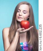 Красивая девушка держит красное яблоко. Стоковое фото, фотограф Nikolay Safronov / Фотобанк Лори