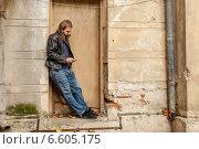 Мужчина с длинными волосами и бородой слушает музыку с телефона, прислонившись к стене (2014 год). Стоковое фото, фотограф Ilie-Cristian IONESCU / Фотобанк Лори