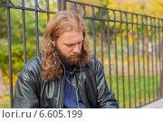 Длинноволосый мужчина с бородой в черной кожаной куртке слушает музыку в наушниках (2014 год). Стоковое фото, фотограф Ilie-Cristian IONESCU / Фотобанк Лори