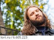 Длинноволосый бородатый мужчина наслаждается музыкой в парке в наушниках (2014 год). Стоковое фото, фотограф Ilie-Cristian IONESCU / Фотобанк Лори
