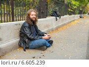 Бородатый мужчина с длинными волосами в кожаной куртке слушает музыку в парке в наушниках, сидя на асфальте (2014 год). Стоковое фото, фотограф Ilie-Cristian IONESCU / Фотобанк Лори