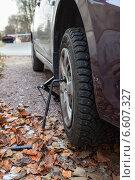 Купить «Автомобиль поднятый на домкрате во время установки зимней резины», фото № 6607327, снято 25 октября 2014 г. (c) Кекяляйнен Андрей / Фотобанк Лори