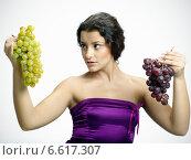 Купить «A woman holding two bunches of white and black grapes.», фото № 6617307, снято 15 февраля 2019 г. (c) BE&W Photo / Фотобанк Лори
