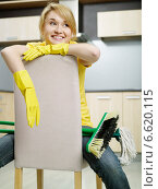 Купить «A tired woman wearing plastic gloves sitting on a chair in the kitchen with a broom and a mop.», фото № 6620115, снято 15 декабря 2018 г. (c) BE&W Photo / Фотобанк Лори