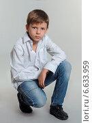 Мальчика в белой рубашке и синих джинсах на сером фоне. Стоковое фото, фотограф Сергей Богданов / Фотобанк Лори