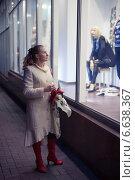 Женщина в белом осеннем пальто рассматривает витрину магазина. Стоковое фото, фотограф Эдуард Данилов / Фотобанк Лори