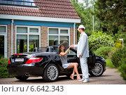 Мужчина подает руку девушке, выходящей из роскошного автомобиля (2014 год). Редакционное фото, фотограф Катерина Вахе / Фотобанк Лори