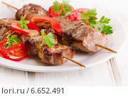 Купить «Pork kebabs served with vegetables on a white plate», фото № 6652491, снято 4 ноября 2014 г. (c) Tatjana Baibakova / Фотобанк Лори