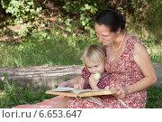 Девочка с яблоком читает книгу с мамой в летнем саду. Стоковое фото, фотограф Мороз Елена / Фотобанк Лори