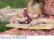 Маленькая девочка смотрит в книгу, которую читает мама. Стоковое фото, фотограф Мороз Елена / Фотобанк Лори