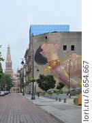 Городской пейзаж с граффити на старом здании и костелом вдали. Польша, Лодзь (2014 год). Редакционное фото, фотограф Ирина Борсученко / Фотобанк Лори