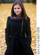 Купить «Весёлая девушка стоит на фоне жёлтых листьев лежащих на земле», эксклюзивное фото № 6667099, снято 15 октября 2014 г. (c) Игорь Низов / Фотобанк Лори