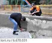 Купить «Субботник во дворе жилого дома: двое мужчин ремонтируют подпорную стену возле детской игровой площадки», фото № 6670031, снято 2 ноября 2011 г. (c) Анна Мартынова / Фотобанк Лори