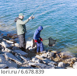 Купить «Отец с сыном ловят форель в озере. Взрослый поймал рыбу, а ребенок помог сачком вытащить ее из воды», фото № 6678839, снято 16 ноября 2014 г. (c) Ирина Кожемякина / Фотобанк Лори