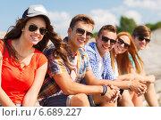 Купить «close up of smiling friends sitting on city street», фото № 6689227, снято 10 августа 2014 г. (c) Syda Productions / Фотобанк Лори