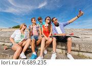 Купить «group of smiling friends with smartphone outdoors», фото № 6689235, снято 10 августа 2014 г. (c) Syda Productions / Фотобанк Лори