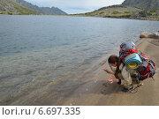 Девушка с туристическим рюкзаком оставляет отпечатки ладоней на песке на берегу озера Байкал. Стоковое фото, фотограф Пыткина Альбина / Фотобанк Лори