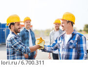Купить «group of smiling builders shaking hands outdoors», фото № 6700311, снято 21 сентября 2014 г. (c) Syda Productions / Фотобанк Лори