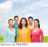 Купить «group of smiling teenagers over blue sky and grass», фото № 6704903, снято 22 июня 2014 г. (c) Syda Productions / Фотобанк Лори