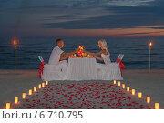 Молодая пара на романтчном ужине при свечах на берегу моря вечером. Стоковое фото, фотограф Елена Кирьян / Фотобанк Лори
