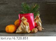 Купить «Подарочный пакет, мандарины, орехи, ветка ели на деревянном фоне», фото № 6720851, снято 24 ноября 2014 г. (c) Marina Kutukova / Фотобанк Лори