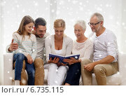 Купить «happy family with book or photo album at home», фото № 6735115, снято 21 августа 2014 г. (c) Syda Productions / Фотобанк Лори