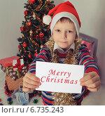 """Мальчик у елки держит в руках открытку """"счастливого рождества"""" Стоковое фото, фотограф Сергей Богданов / Фотобанк Лори"""