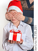 Мальчик держит коробку с подарком, мама закрывает ему глаза. Стоковое фото, фотограф Сергей Богданов / Фотобанк Лори