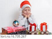 Грустный мальчик смотрит на новогодние подарки. Стоковое фото, фотограф Сергей Богданов / Фотобанк Лори