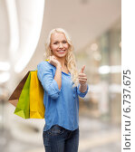 smiling young woman with shopping bags. Стоковое фото, фотограф Syda Productions / Фотобанк Лори