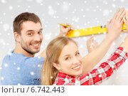 Купить «couple building using spirit level to measure», фото № 6742443, снято 26 января 2014 г. (c) Syda Productions / Фотобанк Лори