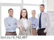 Купить «smiling businesswoman in office with team on back», фото № 6742487, снято 5 апреля 2014 г. (c) Syda Productions / Фотобанк Лори