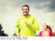 Купить «smiling couple running outdoors», фото № 6742727, снято 3 июля 2014 г. (c) Syda Productions / Фотобанк Лори
