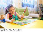 Девочка-левша рисует большим карандашом, сидя за столом (2012 год). Редакционное фото, фотограф Наталья Федорова / Фотобанк Лори