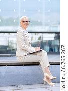 Купить «young smiling businesswoman with notepad outdoors», фото № 6765267, снято 19 августа 2014 г. (c) Syda Productions / Фотобанк Лори