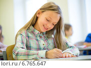 Купить «smiling school girl writing test in classroom», фото № 6765647, снято 15 ноября 2014 г. (c) Syda Productions / Фотобанк Лори