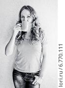 Купить «Девушка в джинсах стоит у стены и пьет кофе из чашки», фото № 6770111, снято 18 сентября 2013 г. (c) Валерия Потапова / Фотобанк Лори