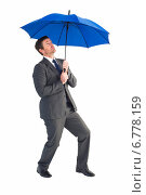 Купить «Businessman sheltering under blue umbrella», фото № 6778159, снято 11 июня 2014 г. (c) Wavebreak Media / Фотобанк Лори