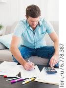Купить «Concentrating man counting his bills», фото № 6778387, снято 11 июня 2014 г. (c) Wavebreak Media / Фотобанк Лори